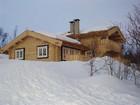 Tradisjonell laftehytte i midten av norsk vinter