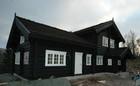 Velstående norsk laftehytte designet i mørkt tre farge som den ser ut på vårparten