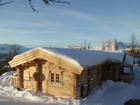 Fasade av vakre Bygdin laftehytte omgitt av snø (1)