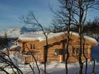 Fasade av vakre Bygdin laftehytte omgitt av snø (2)