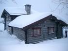 Fasade av Holmen laftehytte på vinteren