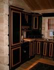 Kitchen of Kvilstoga laftehytte designed in dark & gold colours