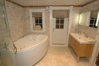 Large bathroom of the laftehytte with bathtub, designed in refined white gamma