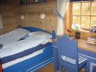 Another bedroom of Kvilstoga laftehytte designed in blue colour